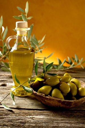olive leaves: olive oil on wood background