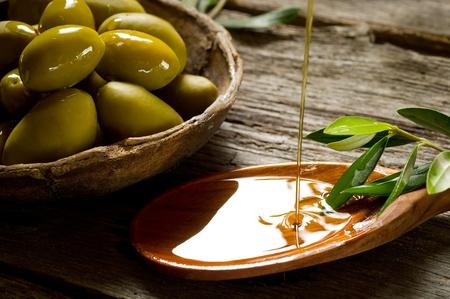 cuchara: el aceite de oliva en el fondo de madera Foto de archivo