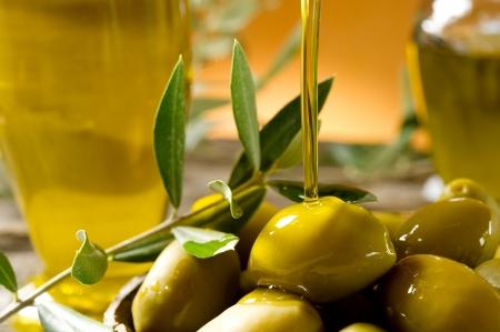 foglie ulivo: olio di oliva su sfondo legno