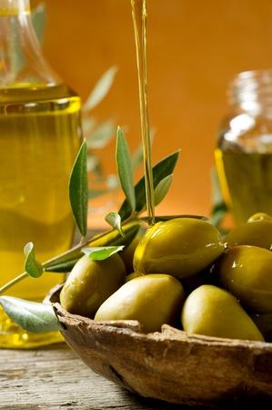 foglie ulivo: olio d'oliva sul fondo di legno