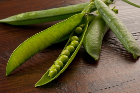 peas and pod over wood background photo