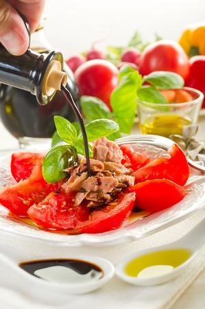 balsamic vinegar over salad with tuna and tomatoes photo