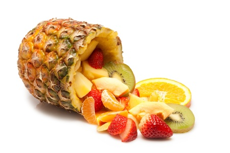 sliced tropical fruits salad on pineapple photo