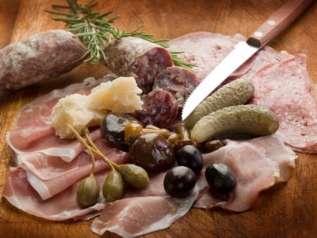 jamon y queso: aperitivo italiano con salami, grana, mota, champiñones, pepino Foto de archivo
