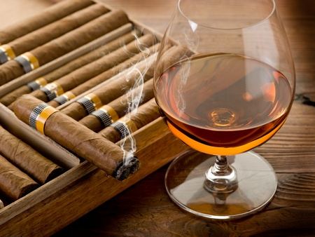 cigar smoke: cuban cigar and cognac on wood background Stock Photo