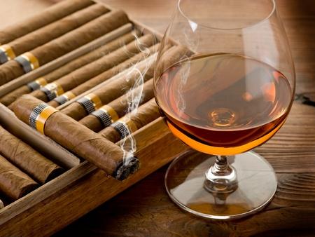 hombre fumando puro: puro cubano y el coñac en el fondo de madera