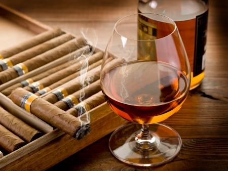 cuban cigar and bottle of cognac on wood background photo