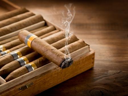 cigarro: fumando cigarro cubano sobre la caja en el fondo de madera