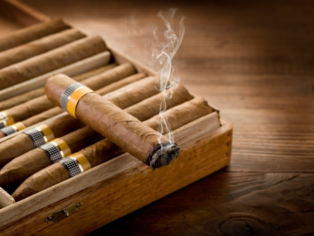 man smoking: smoking cuban cigar over box  on wood background