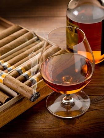 cigar smoking man: cigarro cubano y botella de cognac sobre fondo de madera