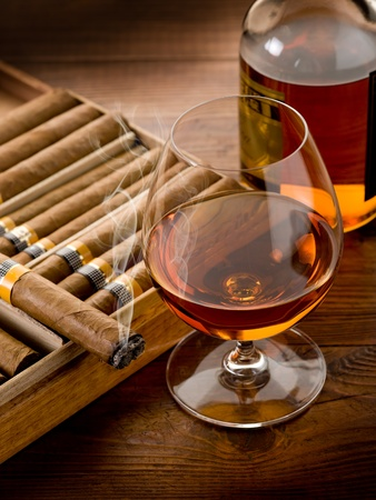 drunks: cuban cigar and bottle of cognac on wood background