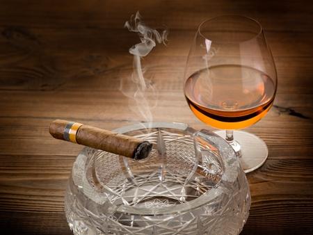 hombre fumando puro: cigarro cubano y cognac sobre fondo de madera