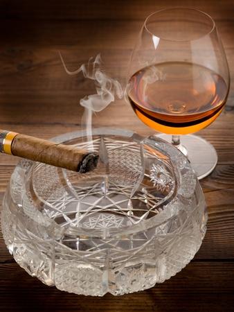 cigar smoke: cuban cigar and cognac on wood background Stock Photo