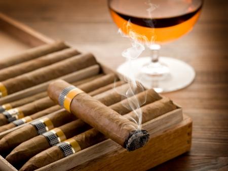 cigar smoking man: cigarro cubano y vaso de licor sobre fondo de madera Foto de archivo