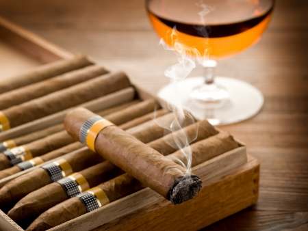 smoking cigar: cuban cigar and glass of  liquor on wood background