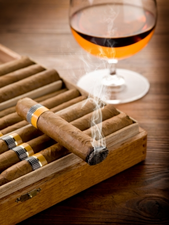 hombre fumando puro: cigarro cubano y vaso de licor sobre fondo de madera Foto de archivo