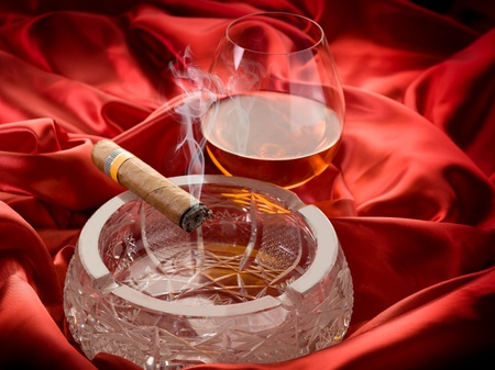 drunks: cuban cigar and  and glass liquor  over red satin