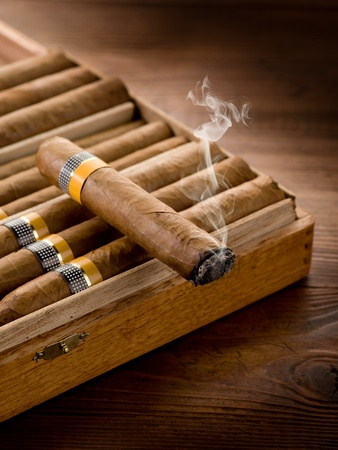smoking cuban cigar over box  on wood background photo