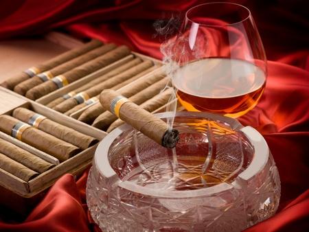 hombre fumando puro: Cigarro cubano y licor sobre la bandeja de cenizas
