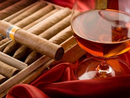 hombre fumando puro: cigarro cubano y licor en sat�n rojo Foto de archivo
