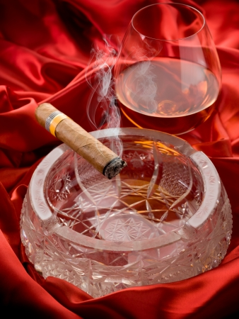 cuban cigar and  and glass liquor  over red satin Stock Photo - 10426637