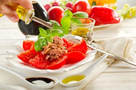 olive oil over salad with tuna and tomatoes photo