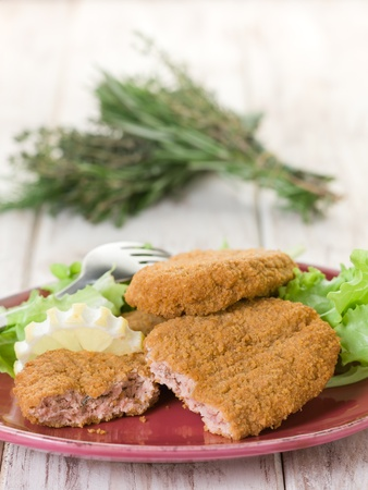 coated: salmon croquettes with green salad Stock Photo