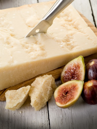 parmesan cheese over cutting board and figs photo