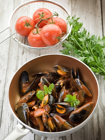 mussel  with tomato sauce and basil over casserole photo