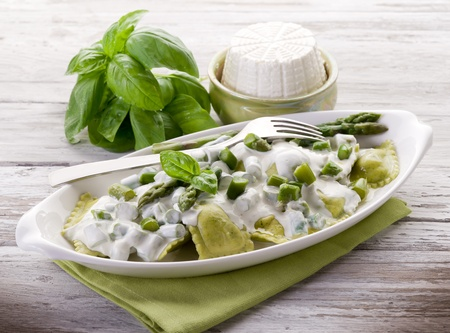 ravioli stuffed with ricotta and basil garnish with cream and asparagus photo