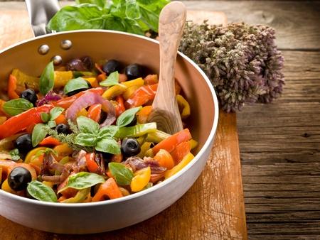 peperonata over casserole on wood background photo