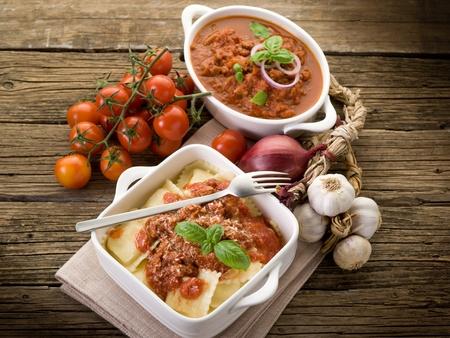 italian cuisine: ravioli with ragout sauce on wooden table Stock Photo