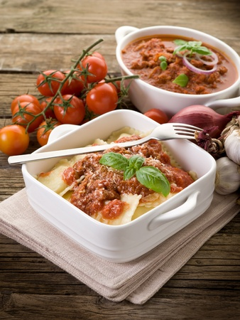 ravioli with ragout sauce on wooden table photo