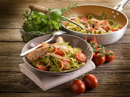 green tagliatelle with norway lobster,  tomatoes and lemon peel photo