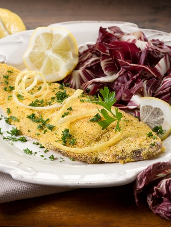 breaded sole with chicory salad and lemon photo