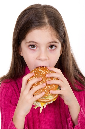 little girl eating hamburger on withe background photo
