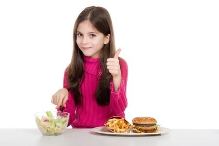 familia comiendo: niña con alimentos saludables y no saludables