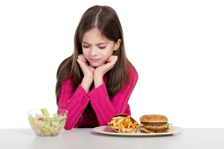 little girl with healthy and unhealthy food photo