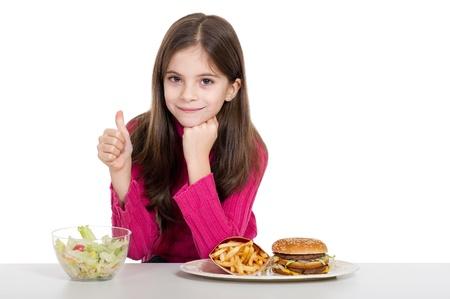 niña con alimentos saludables y no saludables Foto de archivo