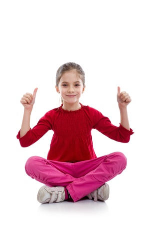 young girl  in relaxed yoga pose with thumbs up photo