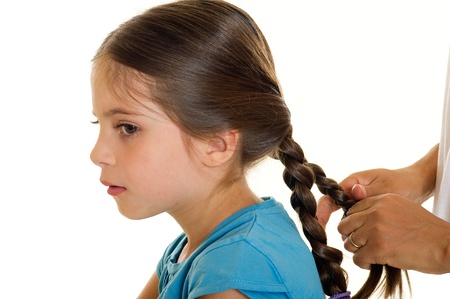 making dresses: making hair braid to little girl Stock Photo