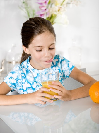 little girl tongue out looking orange juice photo