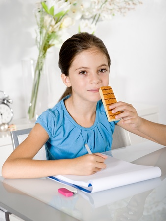 child eats snack while studying photo
