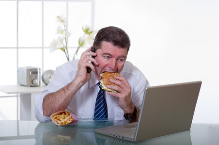 junk: manager eating unhealthy food at work place Stock Photo