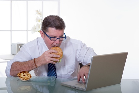 manager eating unhealthy food at work place photo