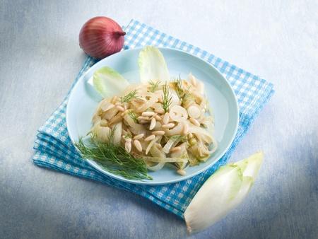 andijvie: salade met gebakken witlof uien en pijnboompitten