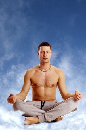 man on yoga position against blue sky Stock Photo - 11856975