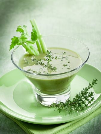 Celery cream soup with thymus on glass photo