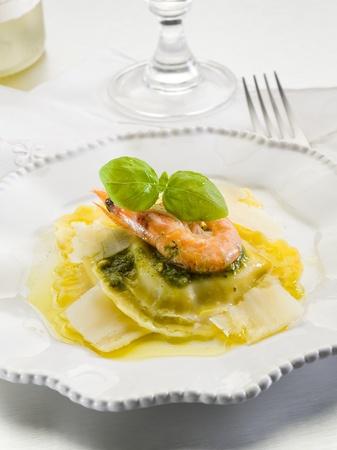 pesto ravioli with shrimp and parmesan flakes photo