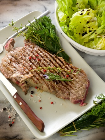 grilled t-bone with green salad photo